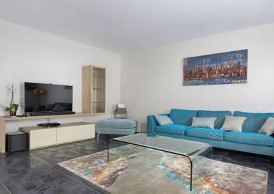 BH-Déco - Sylvie Samain - salon canapé turquoise et bois sur carrelage noir murs lin