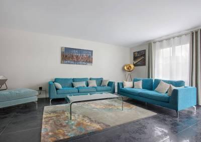 BH-Déco - Sylvie Samain - salon 2 canapés turquoise et bois sur carrelage noir
