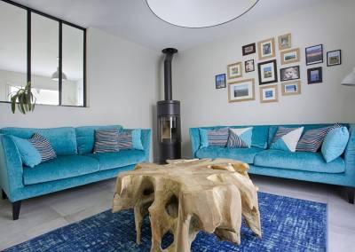 BH-Déco - Sylvie Samain - Salon contemporain bleu turquoise poêle verrière mur de tableaux table racine de teck